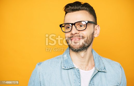 649754038 istock photo Close up portrait of handsome beard man in glasses isolated on yellow background 1148667078
