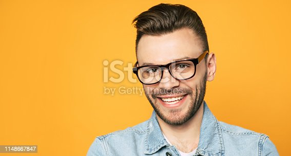 649754038 istock photo Close up portrait of handsome beard man in glasses isolated on yellow background 1148667847