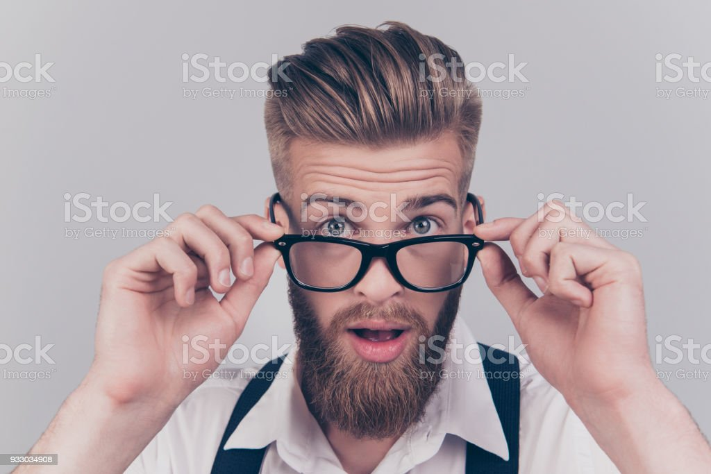 Close up portrait of handsome virile masculine emotion expressing groomed classy smart intelligent clever manager with big eyes touching rimmed glasses isolated on gray background stock photo
