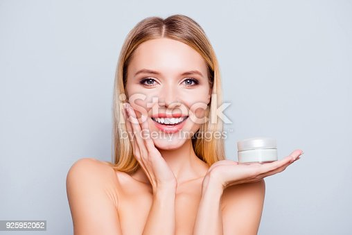 istock Close up portrait of happy gorgeous smiling attractive satisfied young woman with beaming smile, she is holding a cream jar and touching her cheek, isolated on grey background 925952052