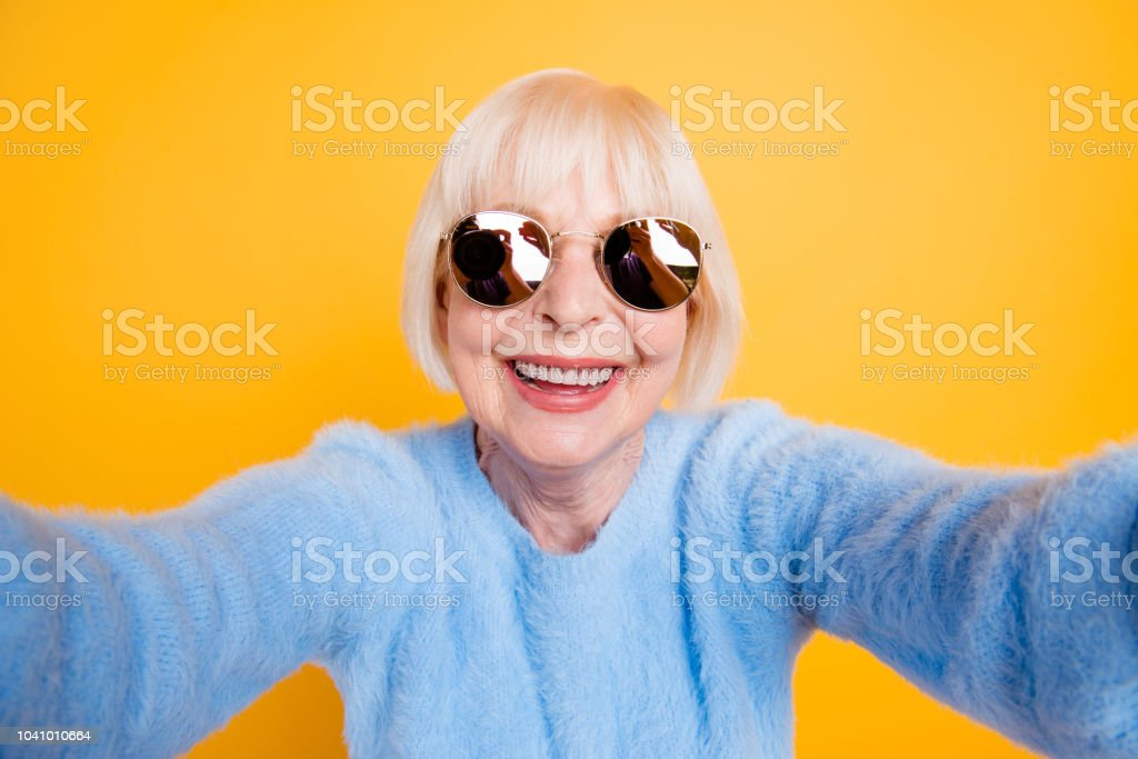 Close up portrait of happy grandma taking a selfie on vacation of two hands, isolated on yellow background royalty-free stock photo