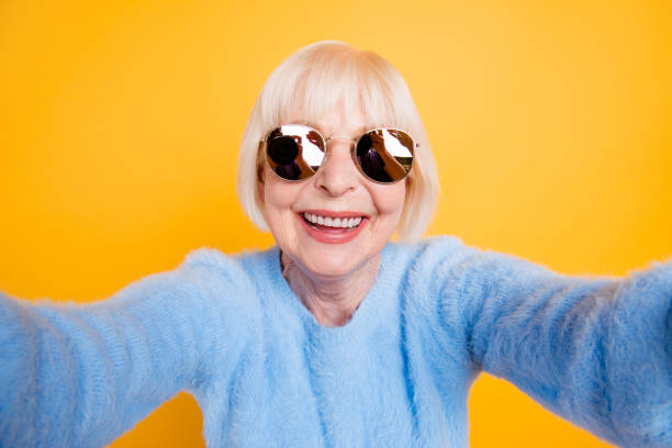 Close up portrait of happy grandma taking a selfie on vacation of two hands, isolated on yellow background Close up portrait of happy grandma taking a selfie on vacation of two hands, isolated on yellow background grandmother stock pictures, royalty-free photos & images