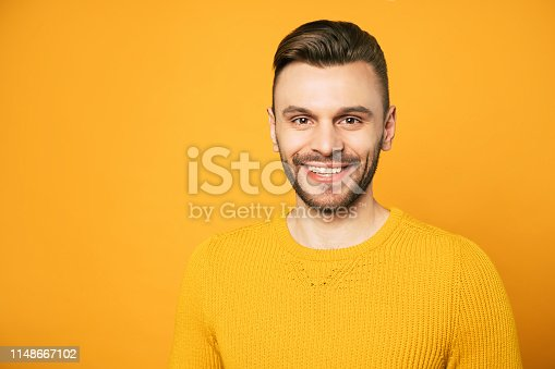906807208 istock photo Close up portrait of happy handsome man in yellow is posing over orange background 1148667102