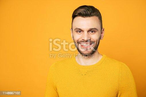 906807208istockphoto Close up portrait of happy handsome man in yellow is posing over orange background 1148667102