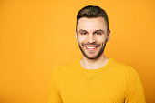 istock Close up portrait of happy handsome man in yellow is posing over orange background 1148667102