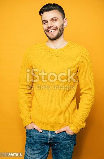 906807208istockphoto Close up portrait of happy handsome man in yellow is posing over orange background 1148667818