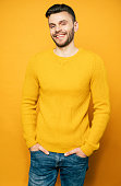 istock Close up portrait of happy handsome man in yellow is posing over orange background 1148667818