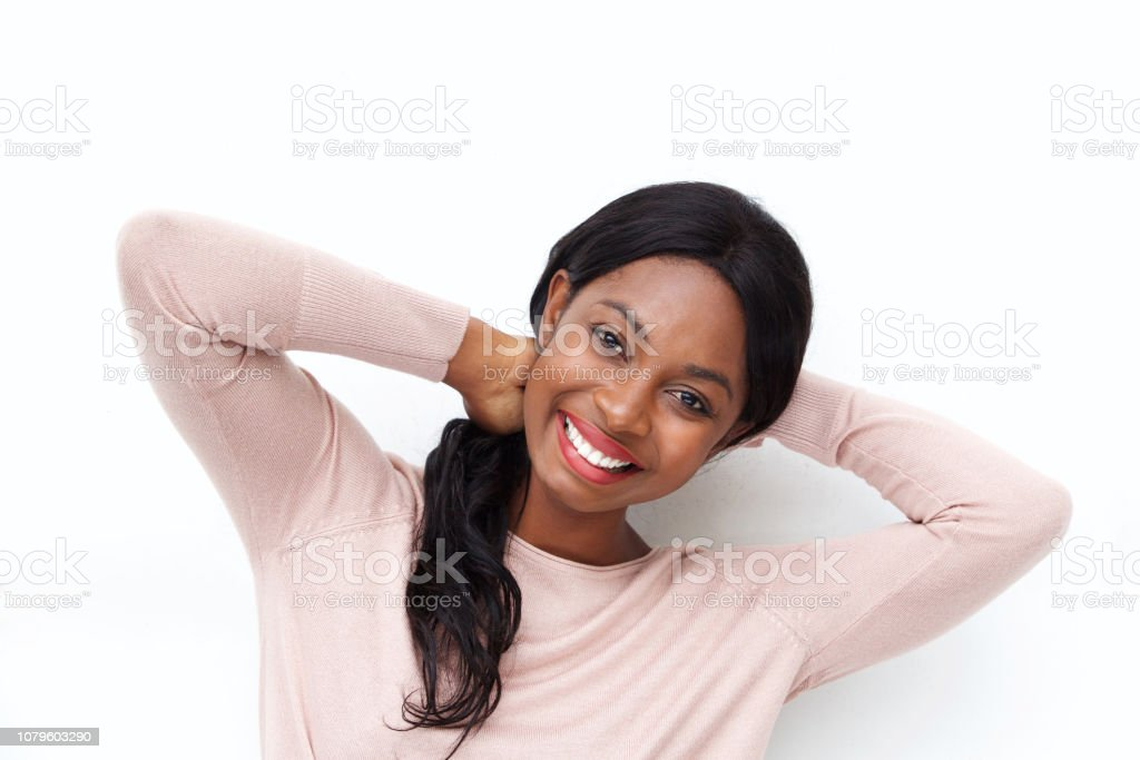 Close up portrait of happy young black woman smiling with hands behind head against white background stock photo
