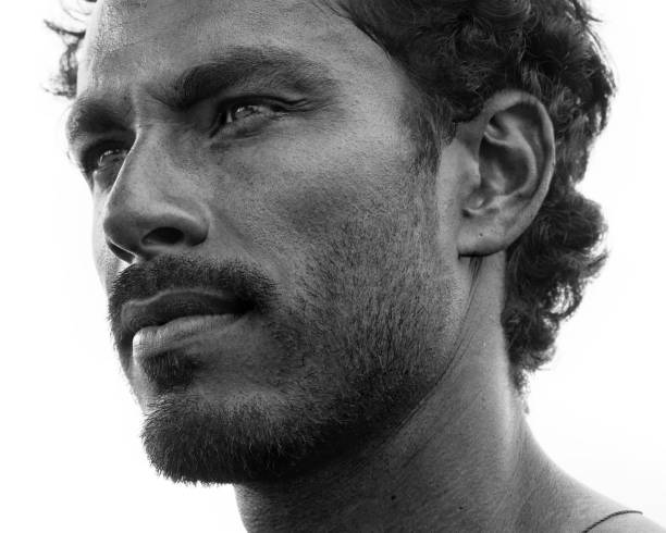 Close up portrait of healthy man with black hair, strong features, looking straight ahead at a three quarters angle, black and white stock photo