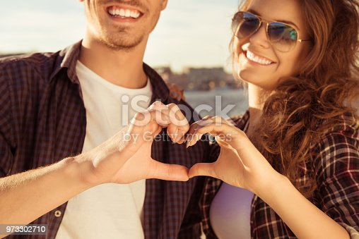 950598260 istock photo Close up portrait of man and woman making heart with fingers 973302710