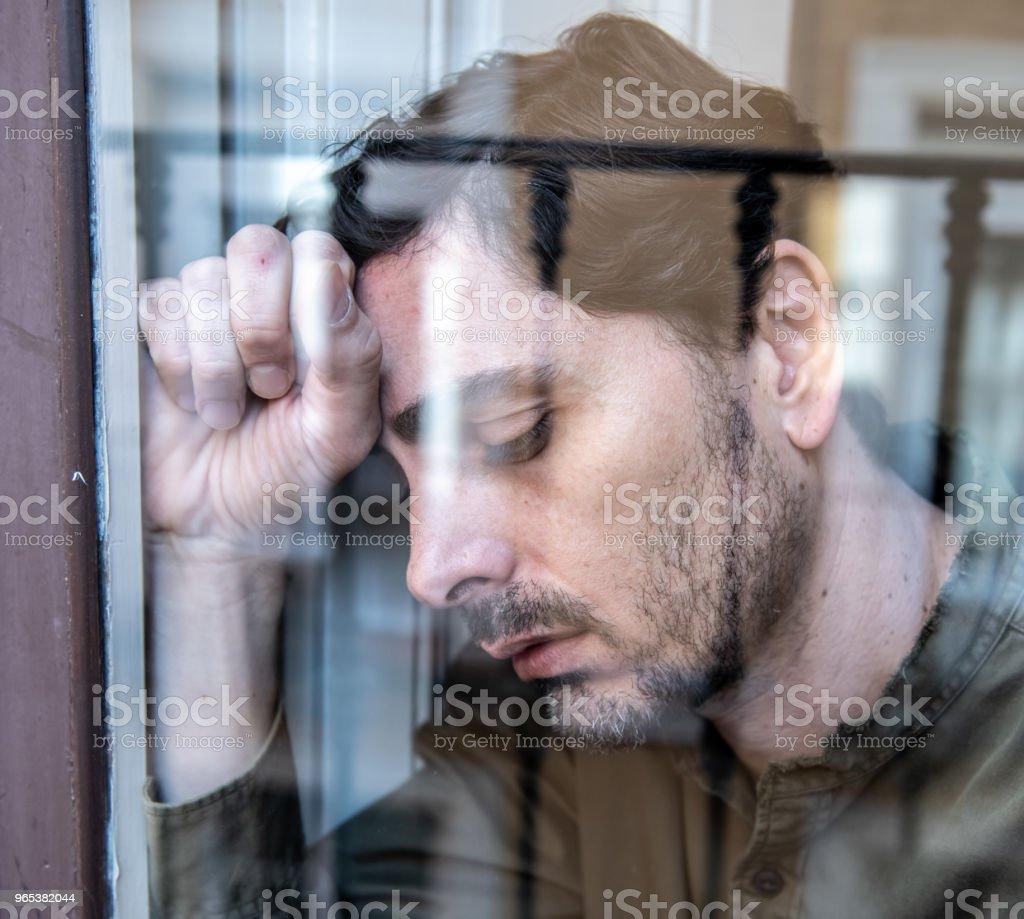 Portrait de moyen de près d'ans homme triste et déprimé regardant à travers la refection de la fenêtre, pensant à sa vie, souffrant de dépression dans le concept de santé mentale - Photo de Adulte libre de droits