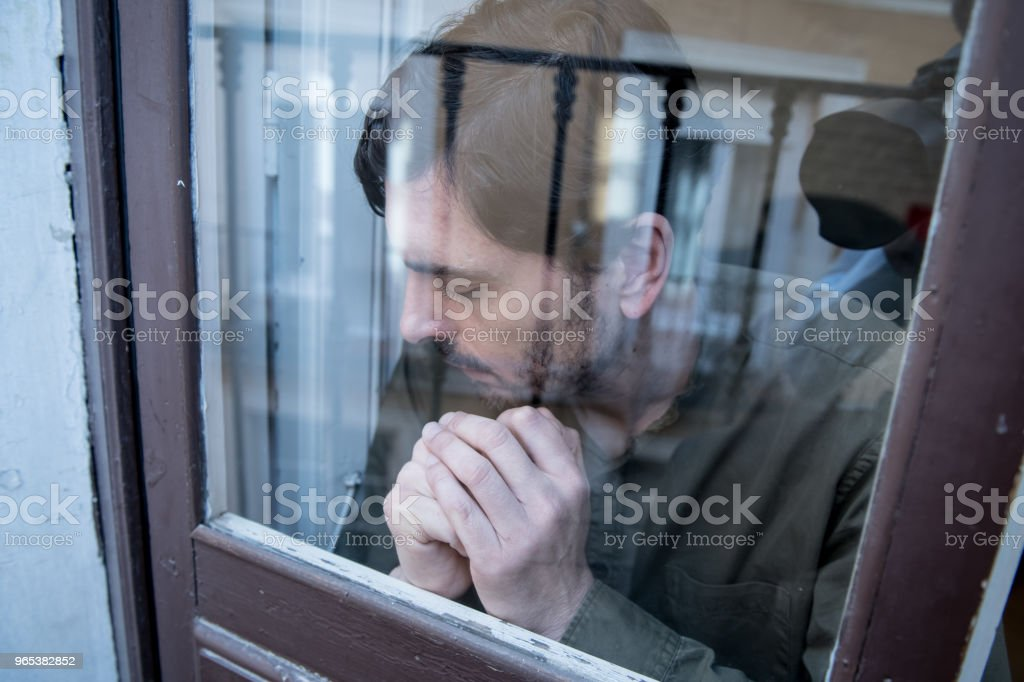 Close up portrait of middle aged man sad and depressed looking through the window refection, thinking about his life suffering depression in mental health concept zbiór zdjęć royalty-free