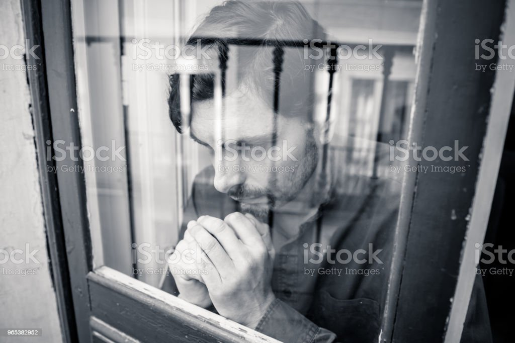 Close up portrait of middle aged man sad and depressed looking through the window refection, thinking about his life suffering depression in mental health concept royalty-free stock photo