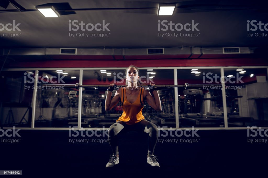 Close up portrait of motivated young shape active fitness woman crouch and doing squad exercise with a bar behind the neck in the gym and looking at the camera. stock photo
