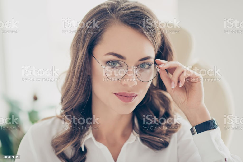 Close up portrait of nice, clever, amazing, trendy, cute, gorgeous financier holding eyelet of glasses on her face with hand looking at camera sitting on armchair in workplace workstation stock photo