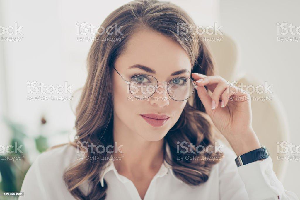 Primer plano retrato de agradable, inteligente, sorprendente, moderno, lindo, hermosa financiero holding ojete de gafas en el rostro con la mano mirando a cámara, sentado en la butaca en la estación de trabajo lugar de trabajo - foto de stock