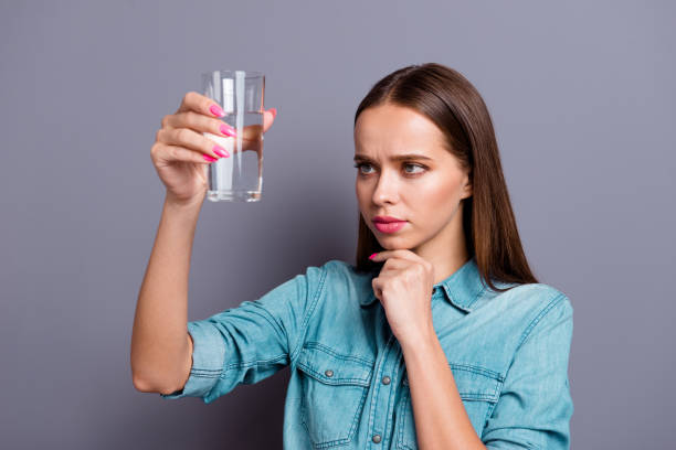Close up portrait of not sure in quality of water she her woman Close up portrait of not sure in quality of water she her woman girl wearing casual jeans shirt outfit clothes isolated on grey background drinking water stock pictures, royalty-free photos & images