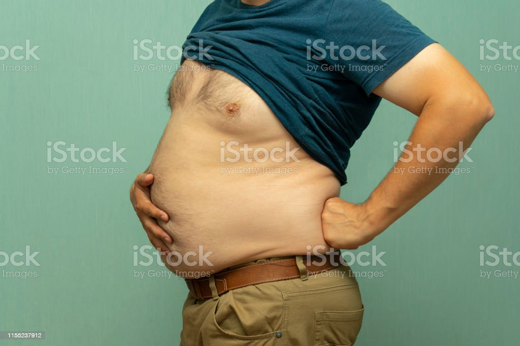 close up portrait of overweight obese man\'s hand holding his big belly