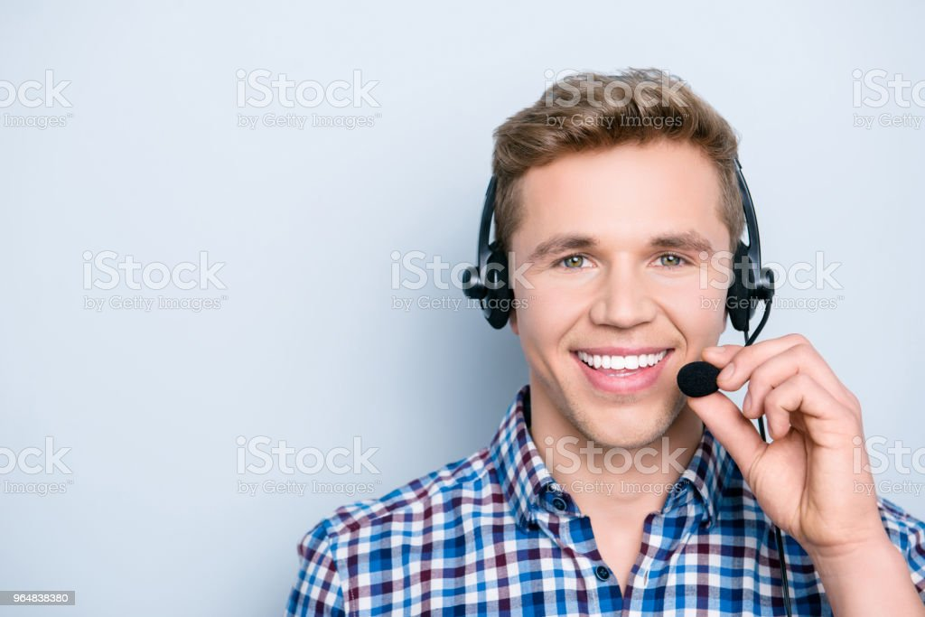 Close up portrait of polite friendly glad cheerful smart clever intelligent  with toothy beaming shiny smile operator using headphones for working isolated on gray background copy-space royalty-free stock photo