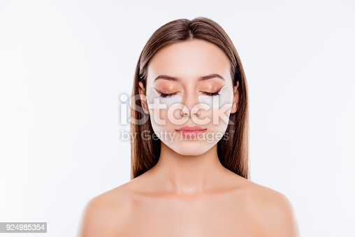 istock Close up portrait of pretty, charming, attractive girl with naked shoulders using, having, applying patches under close eyes, fight with dark circles, standing over white background, wellbeing concept 924985354