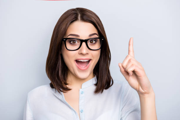 close up portrait of pretty, charming, glad woman in shirt, eyewear finding an idea, resolution, showing index finger up with open mouth, isolated on grey background - finger point stock photos and pictures