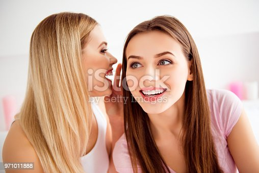 Close up portrait of pretty, successful, confident, charming two girls holding hands near face, blonde telling funny, comic gossip on ear to attentive blonde who listening carefully