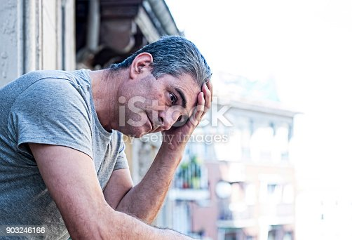 istock close up portrait of sad and depressed 40s man looking through outdoors at home balcony lonesome and thoughtful suffering depression thinking and feeling low in city buildings urban background 903246166