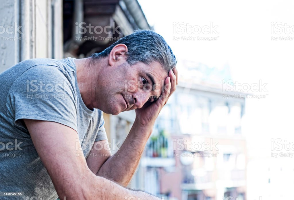close up portrait of sad and depressed 40s man looking through outdoors at home balcony lonesome and thoughtful suffering depression thinking and feeling low in city buildings urban background stock photo