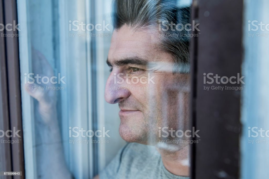close up portrait of sad and depressed 40s man looking through window...