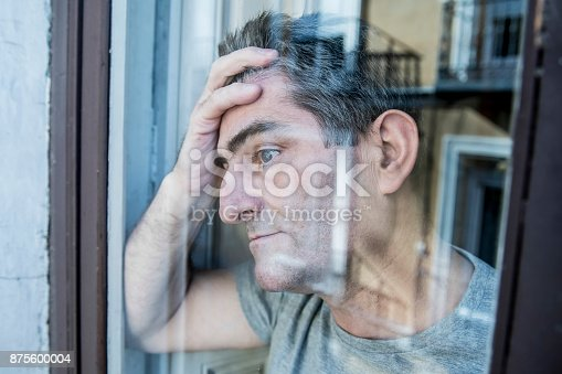 istock close up portrait of sad and depressed 40s man looking through window glass reflection lonesome and thoughtful suffering depression thinking and feeling low i 875600004
