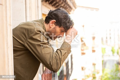 Close Up Portrait Of Sad And Depressed Man Looking Out The Window On A Balcony At Home Suffering Depression And Felling Lonely In Mental Health Concept Stock Photo & More Pictures of 40-49 Years
