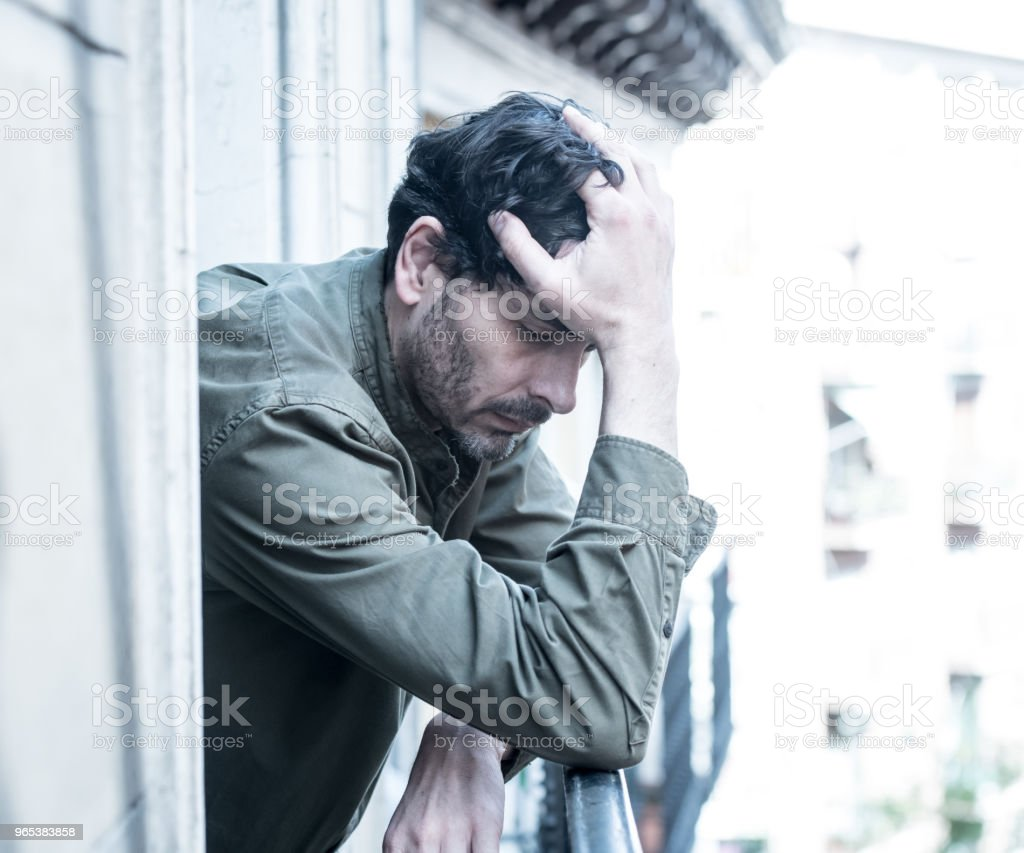 close up portrait of sad and depressed man looking out the window on a balcony at home suffering depression and felling lonely in mental health concept zbiór zdjęć royalty-free