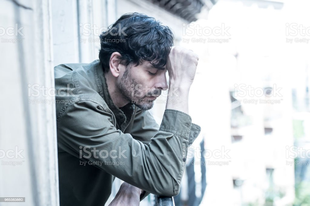 close up portrait of sad and depressed man looking out the window on a balcony at home suffering depression and felling lonely in mental health concept royalty-free stock photo