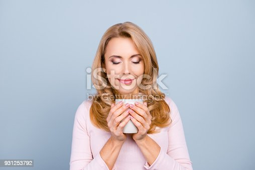 istock Close up portrait of satisfied pretty peaceful delightful calm woman is smelling aromatic cacao isolated on gray background 931253792