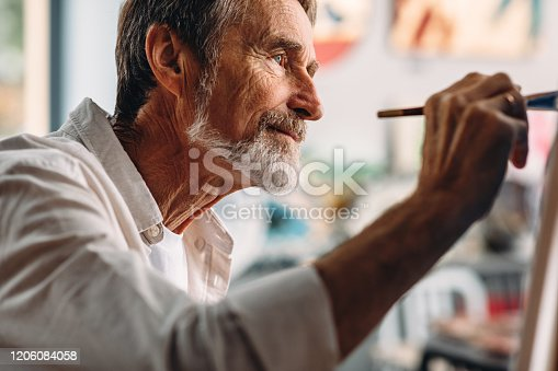 Close up portrait of senior painter drawing on canvas in studio