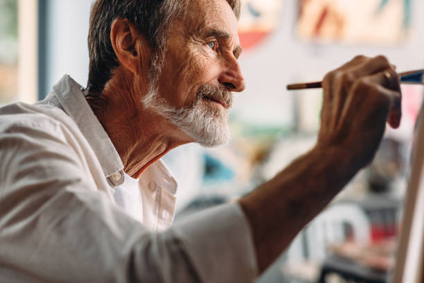 Close up portrait of senior painter drawing on canvas in studio stock photo