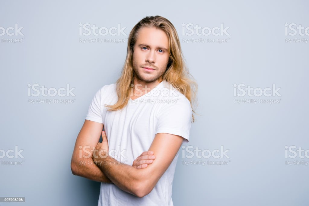Close up portrait of serious and confident young guy with bristle and long blonde hair, he is standing with crossed arms over grey shadeless background - foto stock