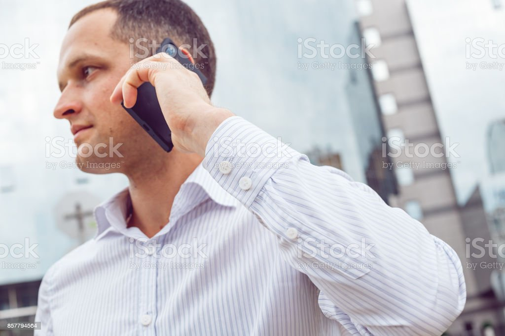 Close up portrait of serious businessman talking on mobile phone. stock photo