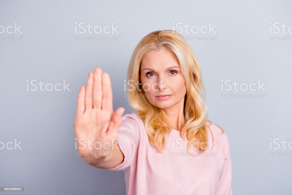 Close up portrait of serious focused concentrated emotion expressing beautiful grandmother granny grandma stretching arm making sign stop with hand modern stylish hairdo isolated on gray background stock photo