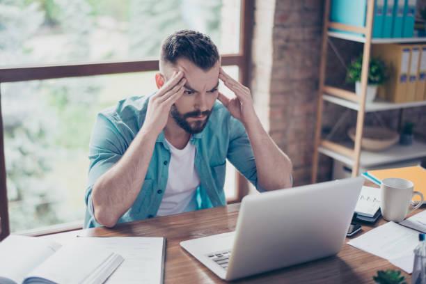 porträt von ernst fokussierte kerl in smart casual jeanshemd, sitzen am schreibtisch im büro nahaufnahme und arbeiten mit laptop. er konzentriert sich mit ideen - druck jeans stock-fotos und bilder