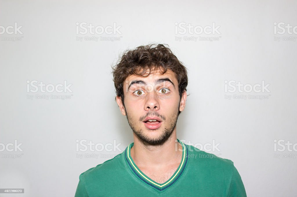 Close up portrait of shocked boy against gray background stock photo