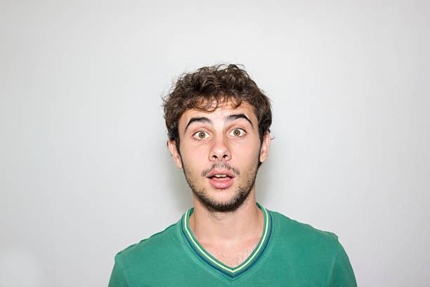 nahaufnahme portrait von überrascht, junge gegen grauen hintergrund - starren stock-fotos und bilder