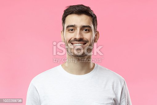 istock Close up portrait of smiling handsome man in white t-shirt isolated on pink background 1022259738