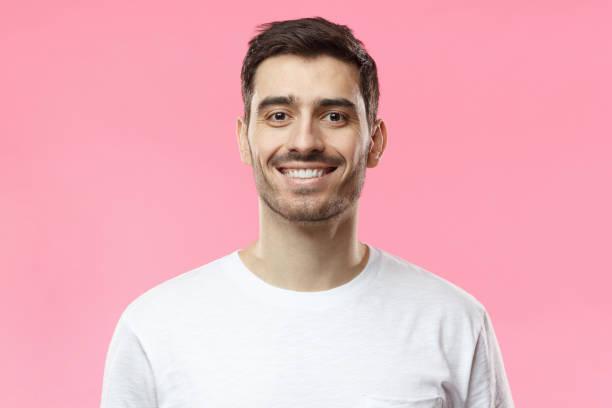 porträt des lächelns gut aussehender mann im weißen t-shirt auf rosa hintergrund isoliert hautnah - mann bart freisteller stock-fotos und bilder