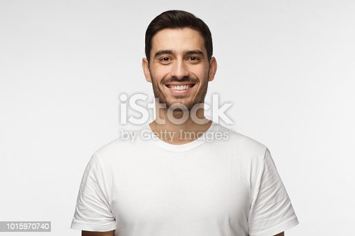 1093999692 istock photo Close up portrait of smiling handsome man in white t-shirt looking at camera, isolated on gray background 1015970740