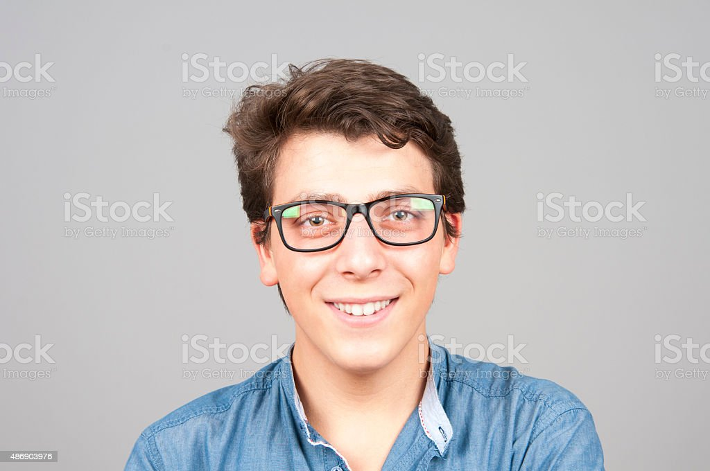 Close up portrait of smiling teenage boy isolated on gray stock photo