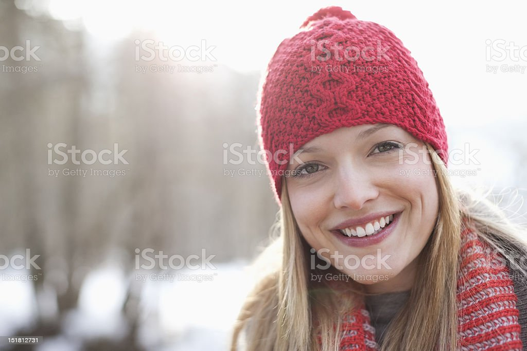Close up portrait of smiling woman wearing red knit hat stock photo