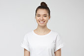 istock Close up portrait of smiling young woman in white t-shirt looking at camera, isolated on gray background 1001505992