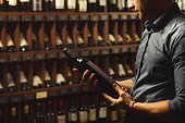 Sommelier holding big wine bottle in hands and looking attentively on it, photo in cellar having collection of containers with alcoholic beverages, dim light and handsome man reading label