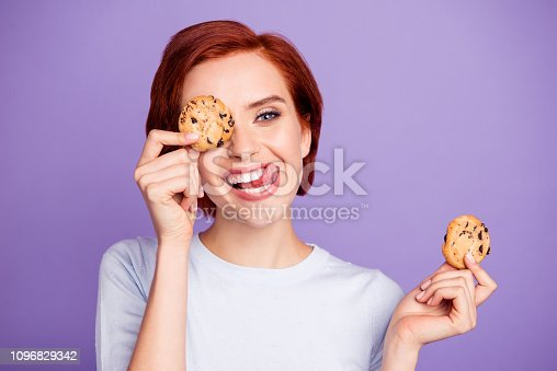 Close up portrait of stylish beautiful pretty cheer cute she her girl hiding eyes behind cookies with stick out tongue loves choco very much isolated on violet background